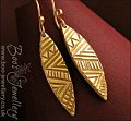 Bronze earrings with a marquise shaped panel, hand carved with tribal patterns