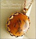 Faux amber cabochon set in a pink bronze bezel pendant